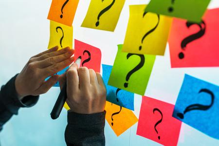 Zakenvrouw die vraagtekens schrijft op kleurrijk plaknotitiepapier op kantoor whiteboard, selectieve focus
