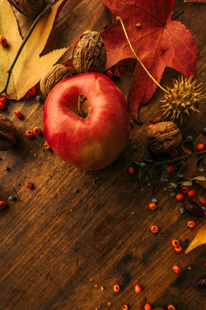 Autumn fruit, berries and leaves on wooden background. Flat lay top view with copy space.