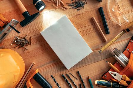 Instruction manual mock up on carpentry woodwork workshop desk, top view