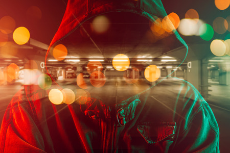 Car thief conceptual image with hooded criminal man overlaying image of underground parking garage Imagens