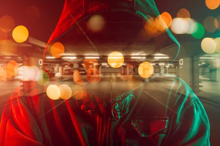 Imagen conceptual de ladrón de autos con hombre criminal encapuchado superponiendo la imagen del estacionamiento subterráneo Foto de archivo