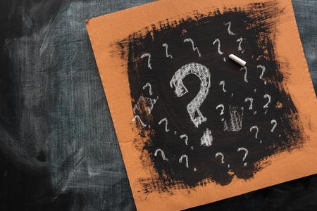 Skizzierte Fragezeichen auf Kartonpapier, Konzept von Verwirrung und Verwirrung