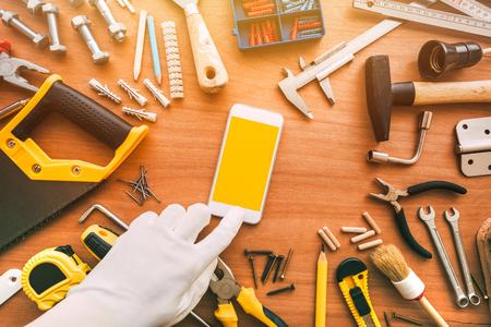 Flatlay-Handwerker-Smartphone-App mit leerem Bildschirm. Mechaniker mit Handy. Kopieren Sie Platz für Text- oder Wartungsarbeiten-Anwendungsnachricht, Ansicht von oben Standard-Bild