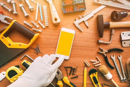 Flatlay handyman smartphone app with blank screen. Repairman using mobile phone. Copy space for text or maintenance work application message, top view Stock Photo