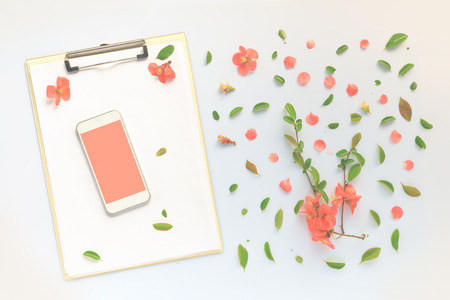 Smartphone and clipboard mock up with colorful springtime floral decoration flat lay top view. Mobile phone blank screen as copy space.