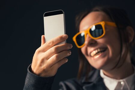 Cool businesswoman making selfie photo portrait with smartphone. Adult caucasian woman in elegant business suit wearing yellow sunglasses is posing in front of mobile phone camera.