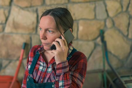 Worried female farmer talking on mobile phone in the stable. Adult woman in plaid shirt and denim overall trousers in telephone conversation.