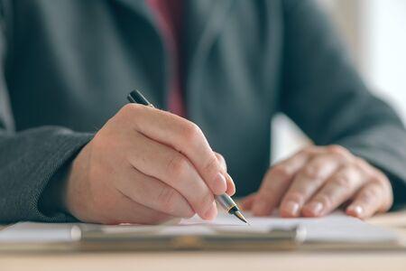 Donna d'affari che firma un contratto e un accordo di partnership commerciale alla scrivania dell'ufficio, primo piano delle mani che scrivono la firma Archivio Fotografico