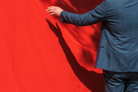 Grand opening, businessman opens red curtain to reveal product. Unrecognizable person with copy space.