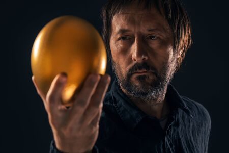Man and golden egg. Valuable business resources and investment opportunity concept. Stock Photo