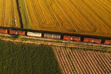 Rail freight transport, aerial view of train passing on railway through cultivated fields in countryside