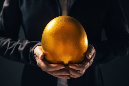 Successful businesswoman holding golden egg as symbol of business opportunity and success Stok Fotoğraf
