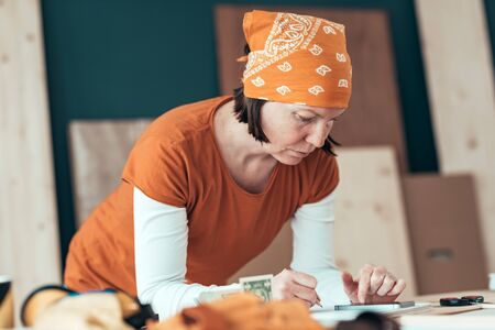 Female carpenter with head kerchief with financial problems in carpentry woodwork workshop, selective focus Stockfoto