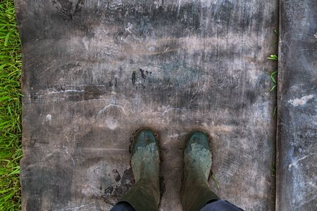 Top view of farmer wearing dirty rubber boots after walking through muddy field