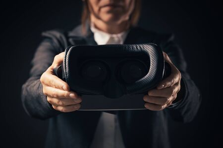 Businesswoman innovator offering VR goggles headset for immersive virtual reality experience