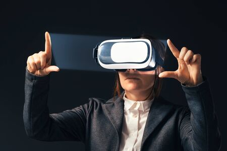 Businesswoman wearing virtual reality headset, digitally enhanced image