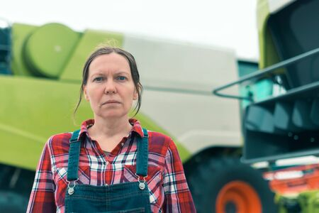 Female farmer posing in front of combine harvester. Serious woman farm worker with agricultural machinery ready harvest crops.