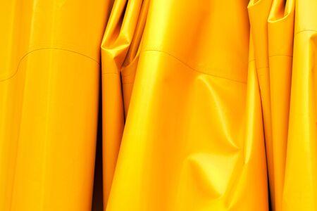 Yellow wrinkled tarpaulin background, artificial tarp material texture