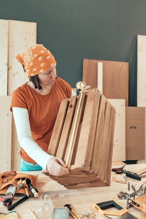 Female carpenter tape measuring wooden crate in her small business woodwork workshop