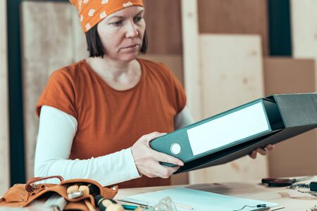 Self employed female carpenter with document ring binder in small business woodwork workshop, selective focus Stockfoto