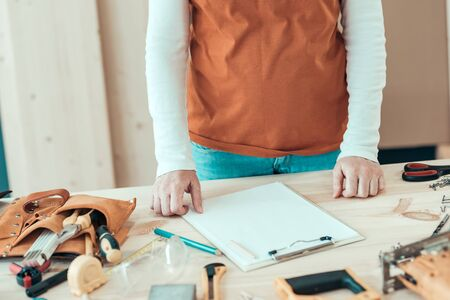 Female carpenter with hands on the desk in small business woodwork workshop