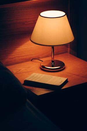 Book and vintage lamp on night table in hotel room. Retro styled bedroom interior.
