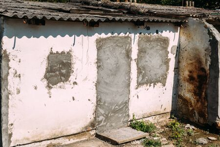 Slum, old ruined houses in poverty neighborhood on sunny summer day