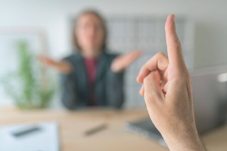 Boss threatening employee with finger in business office, conceptual image with selective focus