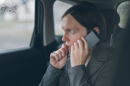 Nervous businesswoman biting nails and talking on mobile phone on back seat of a car