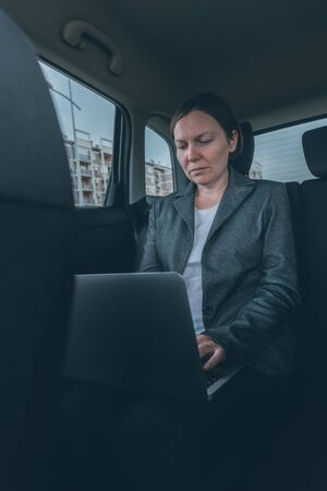 Businesswoman using laptop computer at back seat of company car, business on the move concept with female entrepreneur using modern technology Reklamní fotografie