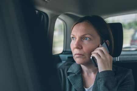 Doubtful businesswoman talking on mobile phone on car back seat, business on the move concept. Elegant adult caucasian female person using smartphone for communication.