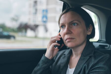 Surprised businesswoman talking on mobile phone on car back seat, business on the move concept. Elegant adult caucasian female person using smartphone for communication.