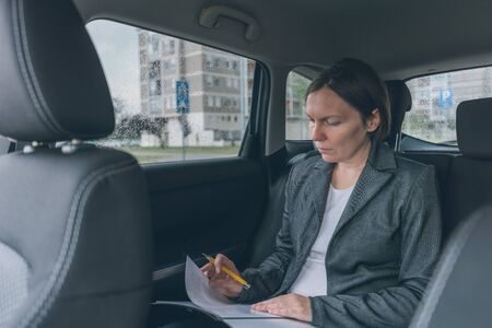Businesswoman doing business paperwork on car back seat, adult caucasian female businessperson executive analyzing business results while traveling by automobile