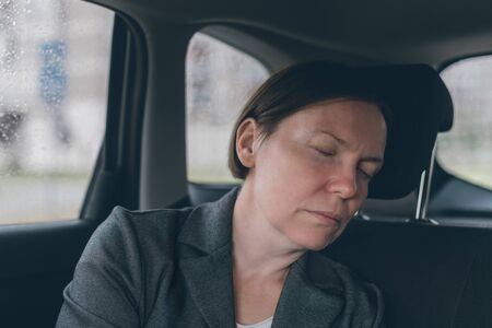 Tired businesswoman sleeping at car back seat, exhausted female executive fallen asleep in corporate limousine Reklamní fotografie