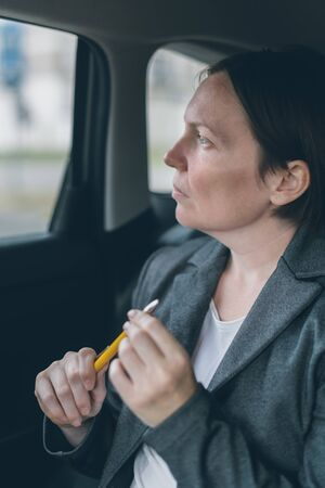 Businesswoman waiting at car back seat and playing with pencil to overcome anxiety Reklamní fotografie