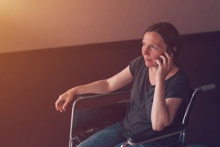 Hopeful female person with disability in wheelchair talking on mobile phone and looking out the window in nursing home