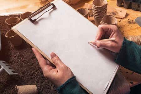 Gardener writing notes on clipboard note paper, mock up blank copy space for text or graphics, preparation for seed planting