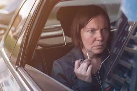 Businesswoman dictating into smartphone earphones microphone while sitting at the back seat of company car