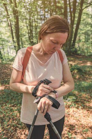 Female hiker checking smart fitness bracelet while trekking through forest