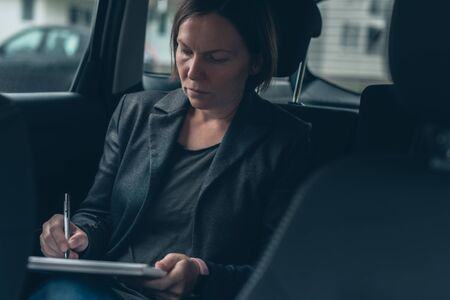 Businesswoman doing paperwork and analyzing business report while sitting in car at the back seat