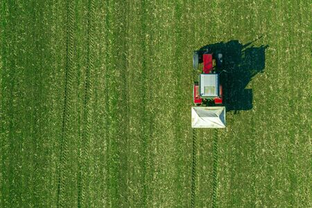 Agricultural tractor is fertilizing wheat crop field with NPK fertilizers, aerial view from drone pov Stock Photo