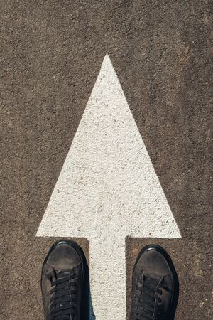 Urban explorer, man in modern shoes standing on asphalt road with white arrow markings and copy space
