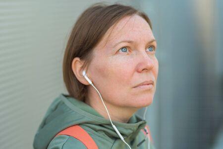 Brisk walker female listening music on earphones, portrait of woman in sports clothing in urban surrounding