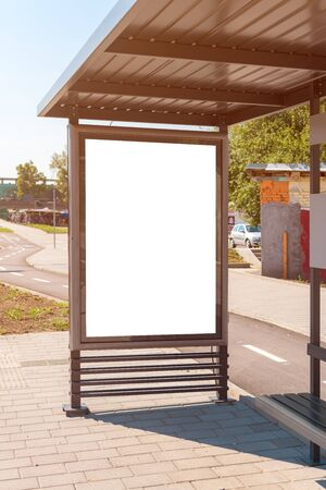 Outdoor advertising poster mock up on bus stop in urban surrounding on bright sunny summer day