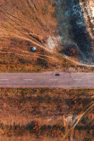 Top view of old worn road through grassy autumn meadow from drone pov Zdjęcie Seryjne