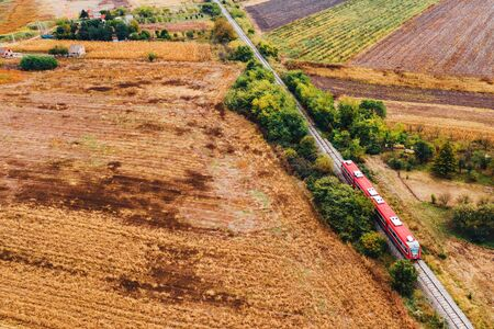 Red passenger train traveling through countryside, aerial view from drone pov in autumn afternoon Zdjęcie Seryjne