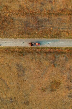 Old tractor on worn asphalt road through grassy countryside meadow, directly above from drone pov Zdjęcie Seryjne
