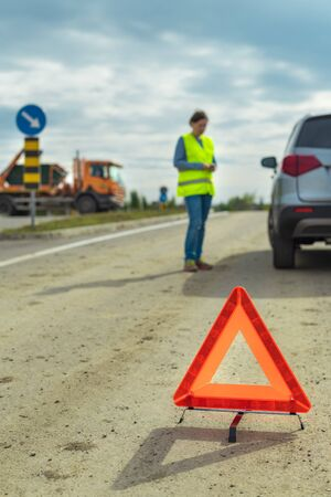 Vehicle breakdown and warning triangle on the road, woman using phone to ask for help and roadside assistance Zdjęcie Seryjne