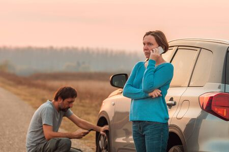 Couple repairing car flat tire on the road in autumn sunset and calling for roadside assistance, selective focus