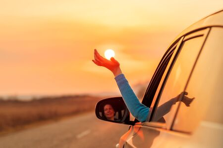 Femme conductrice mettant la main hors de la fenêtre de la voiture tout en conduisant au chaud coucher de soleil d'automne, profitant de la balade et sentant le vent Banque d'images